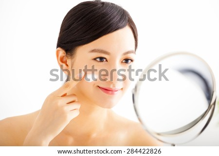 smiling woman applying cream lotion on face - stock photo
