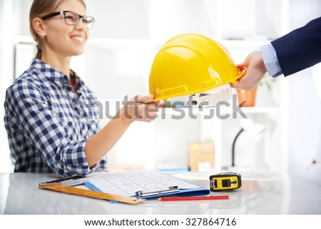 Smiling woman architect giving hardhat to male entrepreneur in office. Business agreement concept. - stock photo