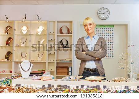 Smiling woman as salesperson behind counter in a jewelry store - stock photo