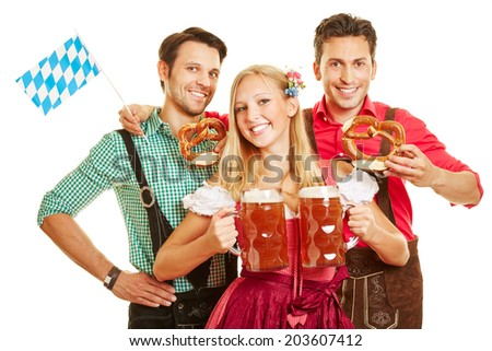 Smiling woman at Oktoberfest carrying two beer glasses in front of two men - stock photo