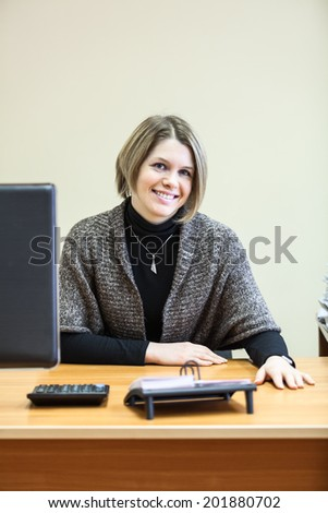 Smiling woman at the desk with computer monitor - stock photo
