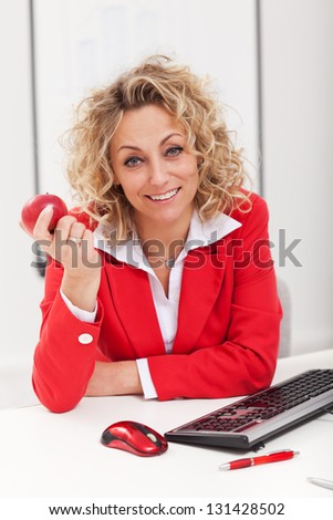 Smiling woman at the office holding apple