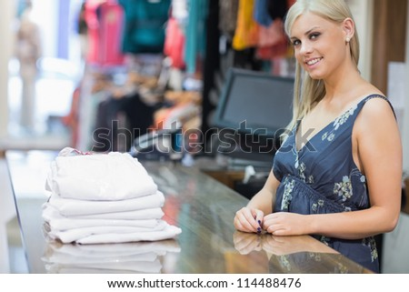 Smiling woman behind counter with folded clothes - stock photo