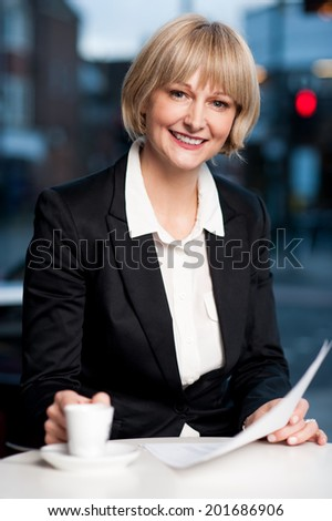 Smiling woman checking business reports carefully in a cafe - stock photo