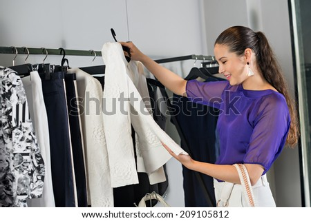 Smiling woman choosing jacket at the clothing store - stock photo