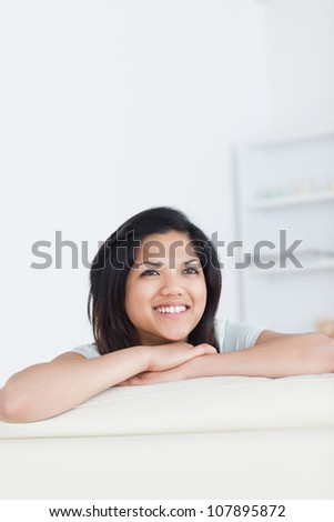 Smiling woman crossing her arms and resting her head on them in a living room - stock photo