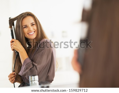 Smiling woman curling hair with straightener - stock photo