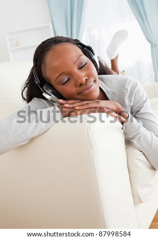 Smiling woman daydreaming while listening to music