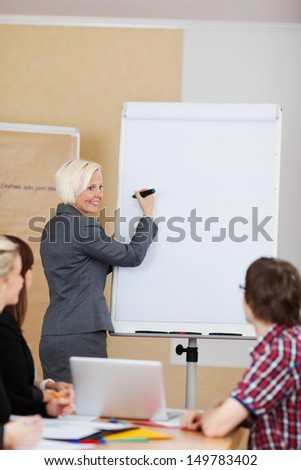 Smiling woman doing a presentation standing at a flipchart with her hand and marker raised to the blank sheet of paper as she turns to smile at her colleagues in the meeting - stock photo