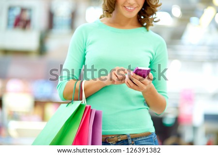 Smiling woman doing shopping and texting on the way - stock photo