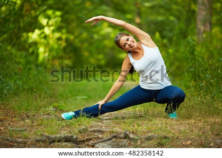 Smiling Woman doing stretching exercise in nature.