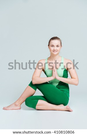 Smiling woman doing yoga exercise isolated on a white background - stock photo
