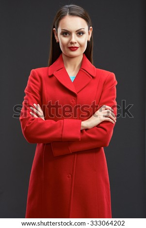 Smiling woman dressed in red coat standing with crossed arms. Studio isolated portrait on dark studio background. - stock photo