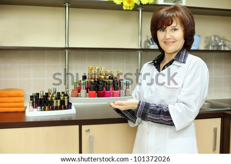 Smiling woman dressed in white robe holds colored nail polish on stand in beauty salon - stock photo