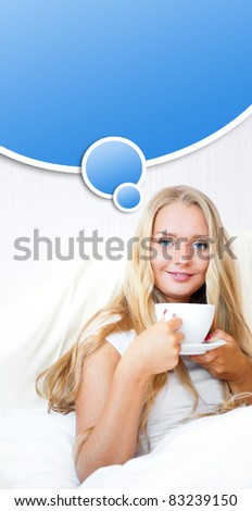 Smiling woman drinking a coffee lying on a bed at home or hotel. Blank balloon with copyspace for your text and logo is same color as eyes of model - stock photo