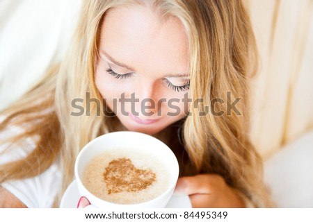 Smiling woman drinking a coffee lying on a bed at home or hotel. Heart shape illustrated on coffee foam. Horizontal shot. Model is breathing aromatic smell of her coffee. Lots of Copyspace. - stock photo