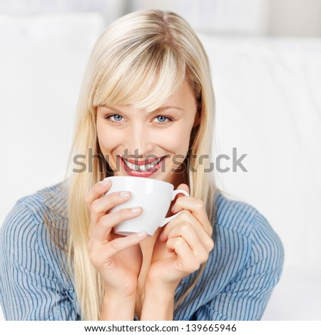 Smiling woman drinking a cup of coffee in a close up shot