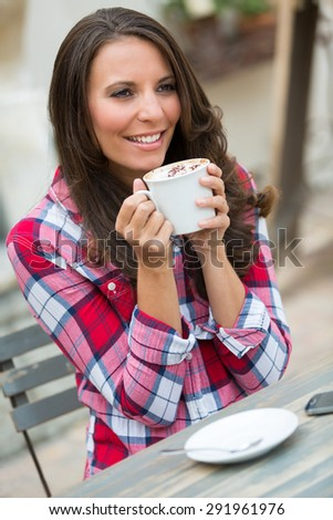 Smiling woman drinking coffee outside - stock photo