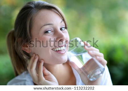 Smiling woman drinking fresh water from glass - stock photo