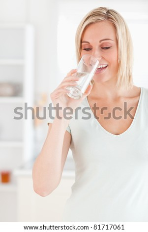 Smiling woman drinking water in the kitchen - stock photo
