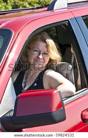 smiling woman drives a red car
