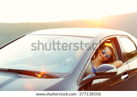 Smiling woman driving a car at sunset. Travel concept