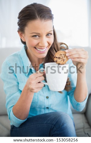 Smiling woman dunking cookie in coffee looking at camera - stock photo