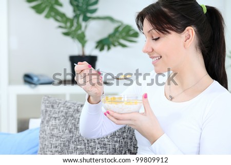 smiling woman eating cornflakes for breakfast - stock photo