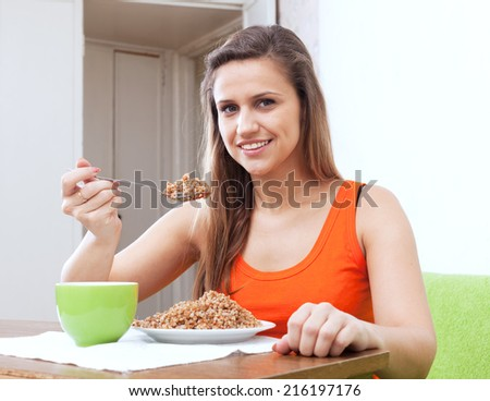 Smiling woman eats buckwheat porridge with spoon at home