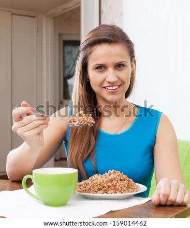 Smiling woman eats buckwheat with spoon at home interior