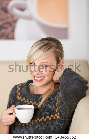 Smiling woman enjoying coffee in a cafe sitting relaxing with a cup of espresso in her hand - stock photo