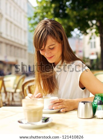 Smiling woman enjoying her espresso in an outdoor coffee shop - stock photo