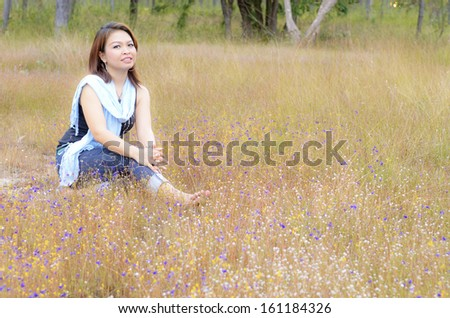 Smiling woman enjoying in field of wild flowers
