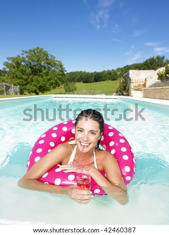 Smiling woman floating in an inner tube and drinking a beverage. Vertical - stock photo