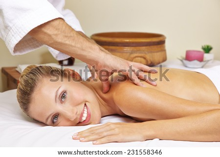 Smiling woman getting back massage in health resort spa - stock photo