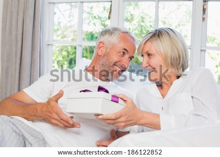 Smiling woman giving mature man a gift box at home