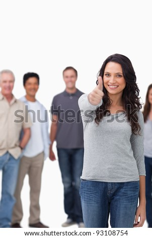 Smiling woman giving thumb up with friends behind her against a white background