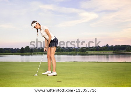Smiling woman golf player putting on green with lake in background. - stock photo