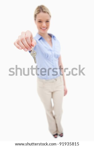 Smiling woman handing over key against a white background - stock photo