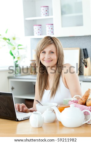 Smiling woman having breakfast in front of the laptop looking at the camera in the kitchen - stock photo