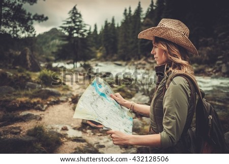 Smiling woman hiker, searching right direction on map near wild mountain river. - stock photo