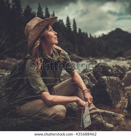 Smiling woman hiker, sitting with map in her hands, near wild mountain river. - stock photo