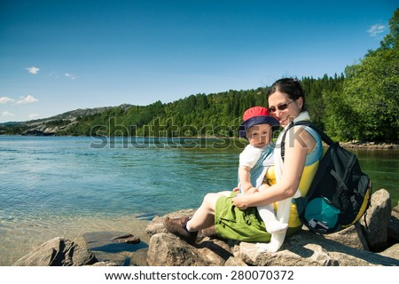 Smiling woman hiker with adorable baby in a sling carrier sitting on a rock next to a mountain lake