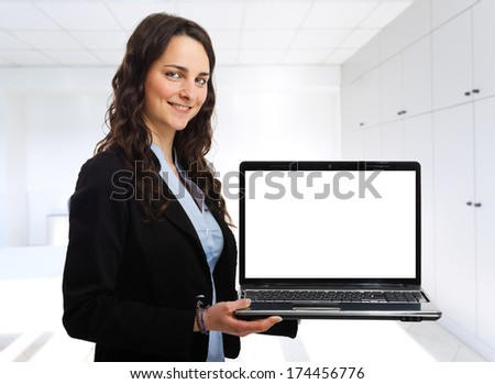 Smiling woman holding a laptop - stock photo