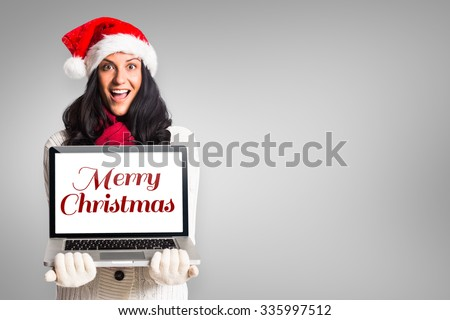 Smiling woman holding a laptop against grey vignette