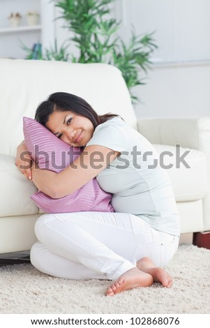 Smiling woman holding a pillow while sitting on the floor in a living room - stock photo