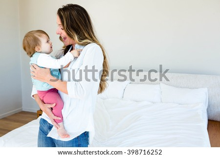smiling woman holding an adorable baby in a bedroom - stock photo