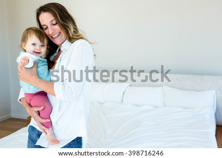 smiling woman holding an adorable baby in her bedroom - stock photo