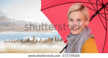 Smiling woman holding an umbrella against large city on the horizon past yellow field - stock photo