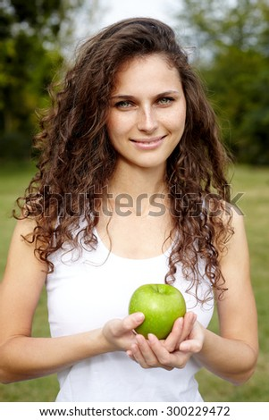 smiling woman holding apple.Outdoor - stock photo